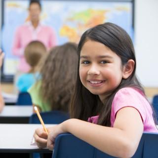Kinder sitzen im Untericht, ein Mädchen dreht sich um und lächelt