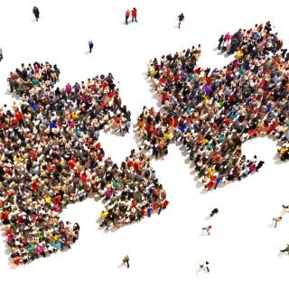 Foto: Große Gruppen von Menschen stellen sich zusammen, damit zwei nebeneinander liegende Puzzleteile entstehen