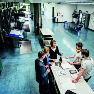 Treffen einer Gruppe von Beschäftigten an einem Tisch in einer Druckerei.