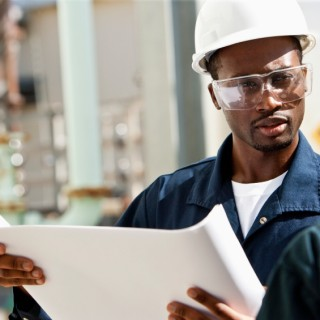 Zwei Personen mit Bauarbeiterhelm und Schutzbrille bei der Arbeit