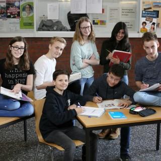 Gruppenfoto mit 7 SchülerInnen gruppiert um Schultisch