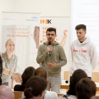 Zwei junge Männer vor Publikum mit Mikrofon