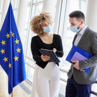 Kollegiales Gespräch zwischen einer Frau und einem Mann auf dem Flur, neben einer EU-Flagge
