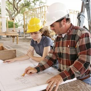 Ausbilder zeigt Auszubildenden auf einem Konstruktionsplan etwas. Sie sind auf einer Baustelle und tragen Bauhelme.