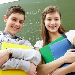 Zwei Schüler stehen lächelnd vor einer Schultafel.