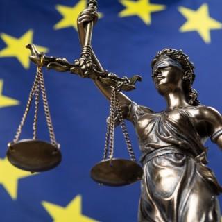 Das Bild zeigt Justitia vor der Europaflagge.