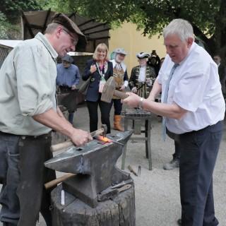 Minister Laumann haut bei seinem Besuch auf dem Flachsmarkt in Krefeld-Linn mit einem Hammer auf einen Amboss