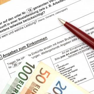 Antragsformular mit Stift und Geldscheinen