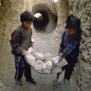 Zwei Kinder in Peru beim Tragen von Steinen