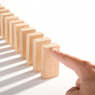 Ein Zeigfinger stößt den ersten Stein einer Reihe Dominosteine an.