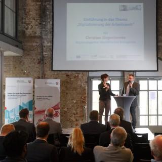 Auf dem Podium: Simone Niewerth und Christian Jürgenliemke - Regionalagentur Westfälisches Ruhrgebiet - Bildschirm mit Veranstaltungstitel
