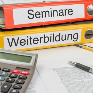"""Schreibtisch mit zwei Aktenordnern mit den Aufschriften """"Seminare"""" und """"Weiterbildung"""""""