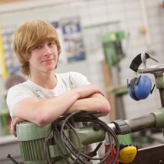 Jugendlicher in Werkstatt - Arme verschränkt über Arbeitsgerät