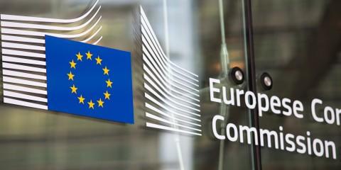 EU-Sterne und Logo EU-Kommission auf Glastür