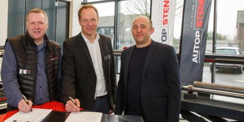 Drei Männer in Showroom der Firma Autopstenhoj mit Unterlagen zur Unterzeichnung