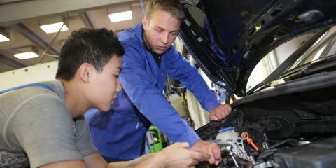 Zwei junge Auszubildende schauen in Motorraum eines Autos