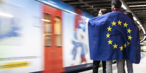 Jugendliche mit EU-Flagge auf Bahnsteig