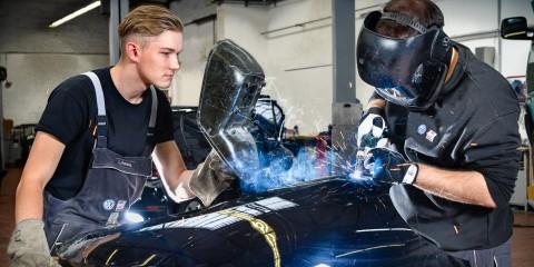 Junger Mann in Arbeitskleidung schaut Kollegen beim Schweißen in der Werkstatt zu