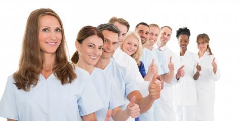 Porträt eines selbstbewussten Pflegeteams. Es steht in einer Schlange hintereinander vor einem weißem Hintergrund und alle strecken den linken Daumen hoch.