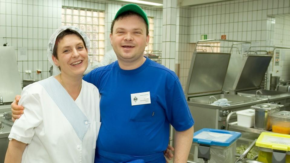 Frau und Mann bei der Arbeit in der Großküche