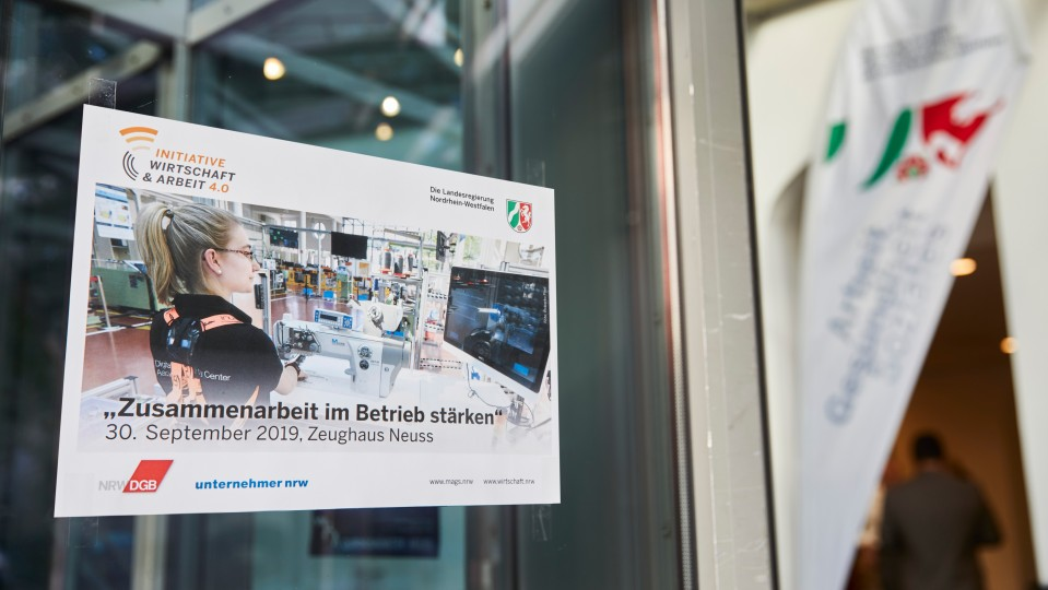"""Plakat mit Titel der Veranstaltung """"Zusammenarbeit im Betrieb"""" an Glastür"""