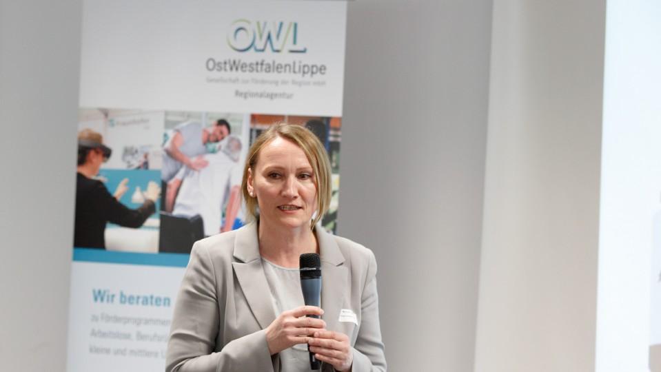 Melanie Taube, Leiterin Regionalagentur OWL, mit Mikrofon