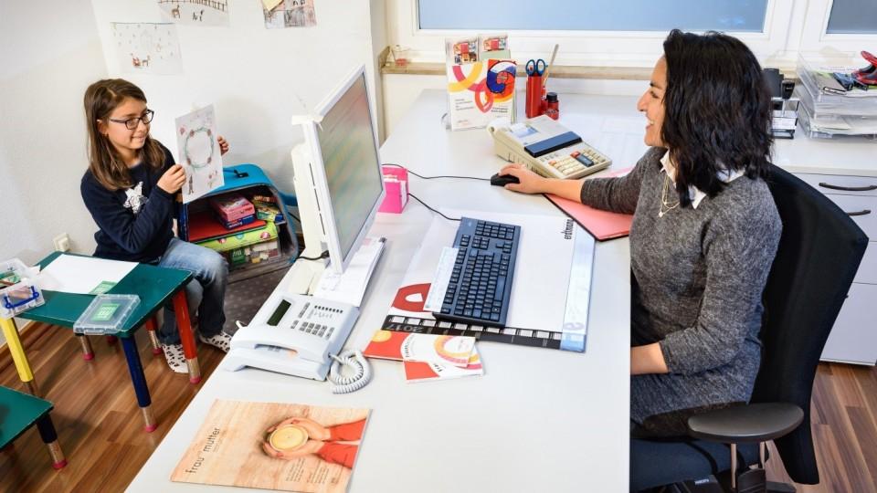 Foto zeigt Auszubildende an ihrem Computerarbeitsplatz und ihre Tochter in einer Spielecke