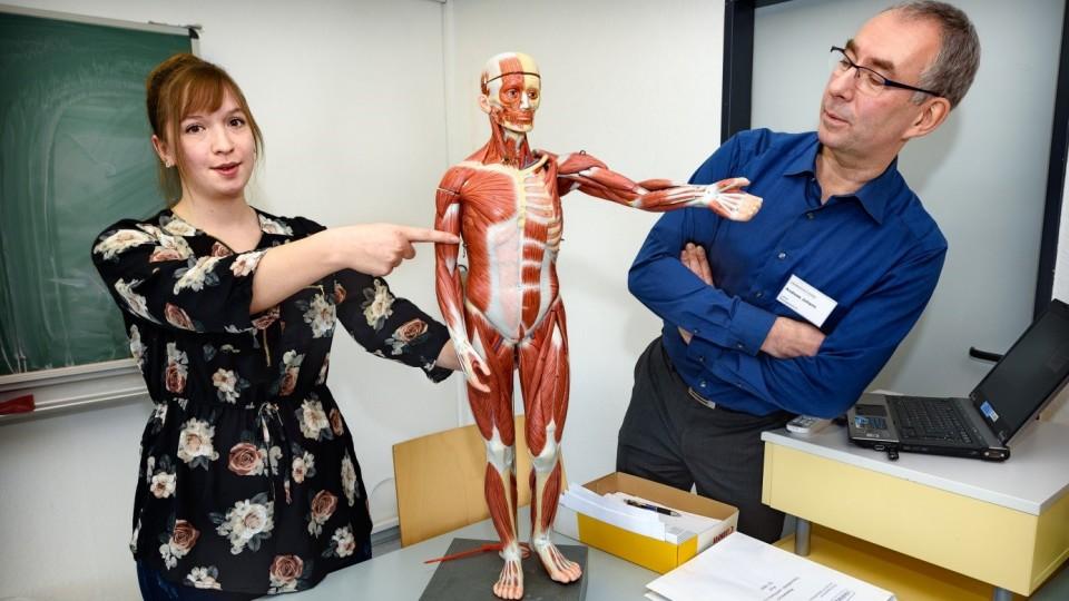 Foto zeigt Auszubildende zur Gesundheits- und Krankenpflegerin zusammen mit Ausbilder und einem Modell