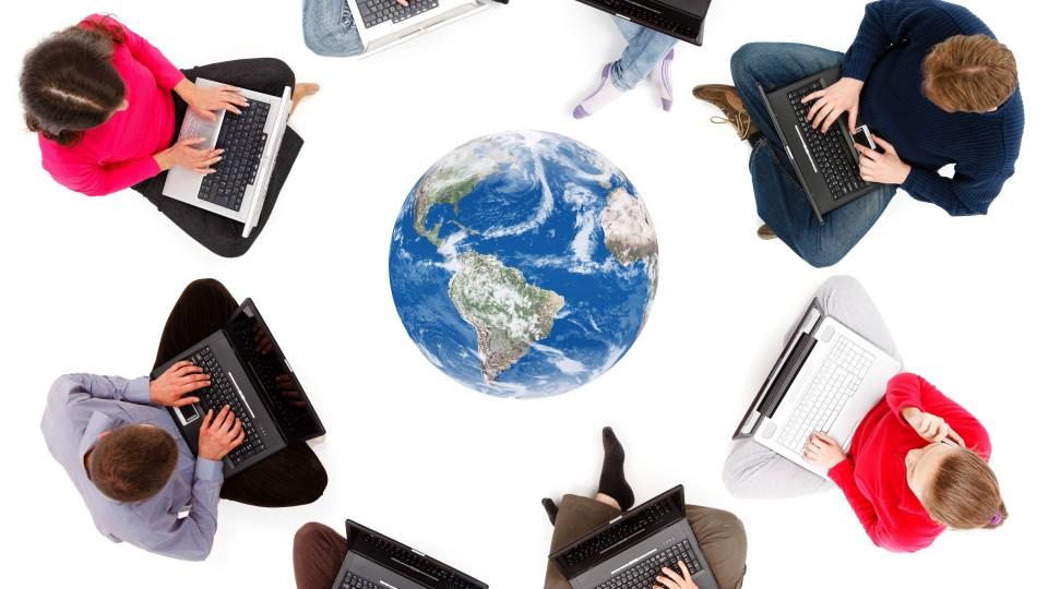 Foto: Menschen mit Laptop sitzen um Weltkugel