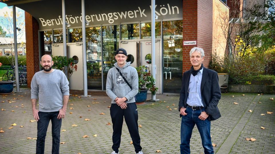 Drei Männer stehen vor einem Gebäude