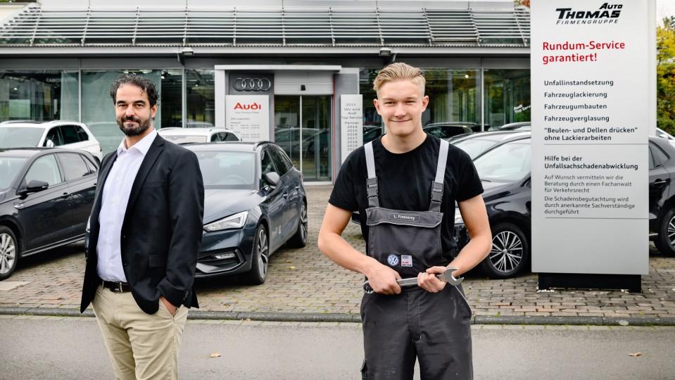 Zwei Männer vor einer Autowerkstatt