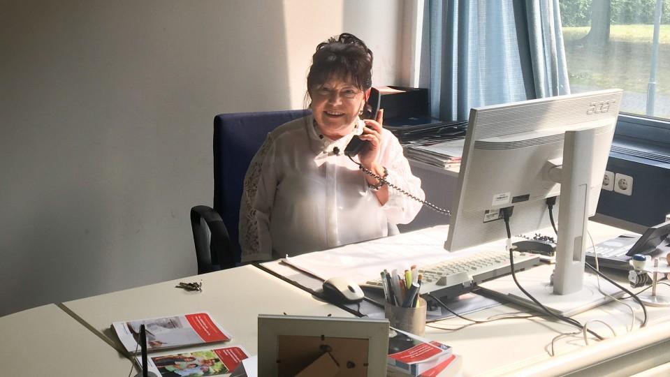 Eine Frau sitzt am Tisch und telefoniert