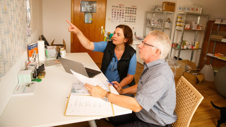 Ausbilderin und Coach studieren den Ausbildungsrahmenplan