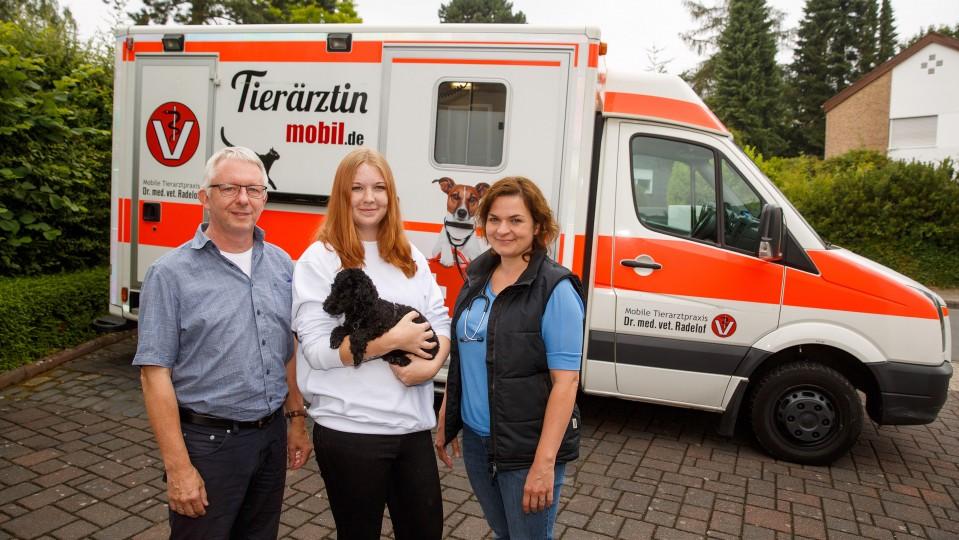 Gesamtfoto: Coach des Projekt, Auzubildende und Tierärztin, im Hintergrund die mobile Tierarztpraxis