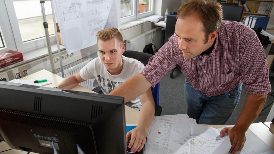 Foto: Marcel Rentzsch mit Ausbilder am PC-Bildschirm.