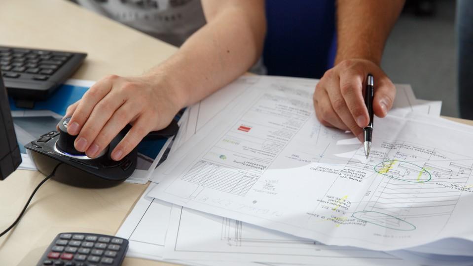 Foto: Detailaufnahme der Hände von Auszubildendem und Ausbilder bei der Arbeit auf dem Schreibtisch.