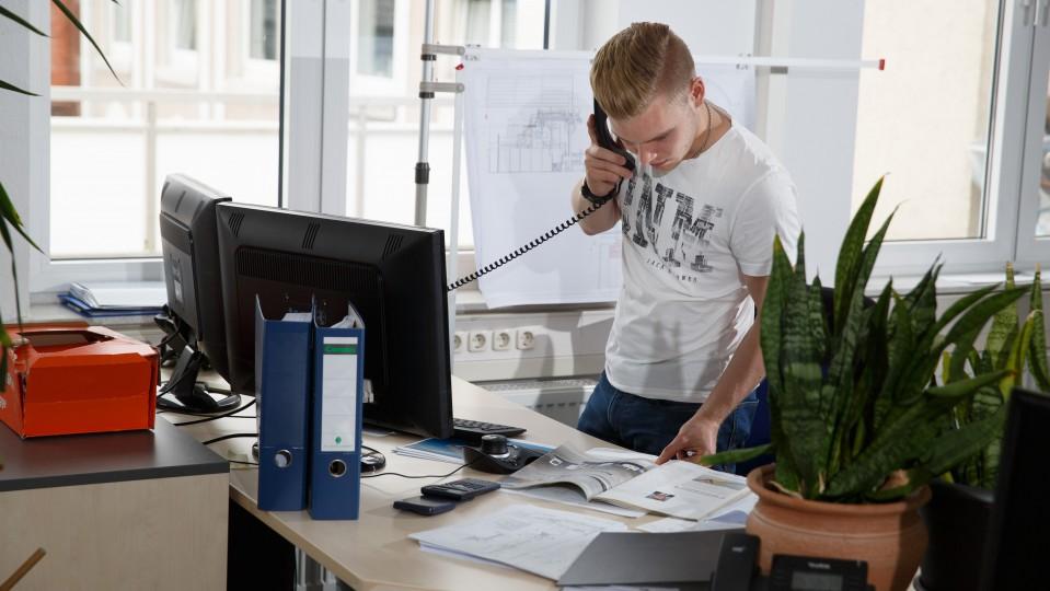 Foto: Auszubildender am Telefon vor dem PC-Bildschirm.