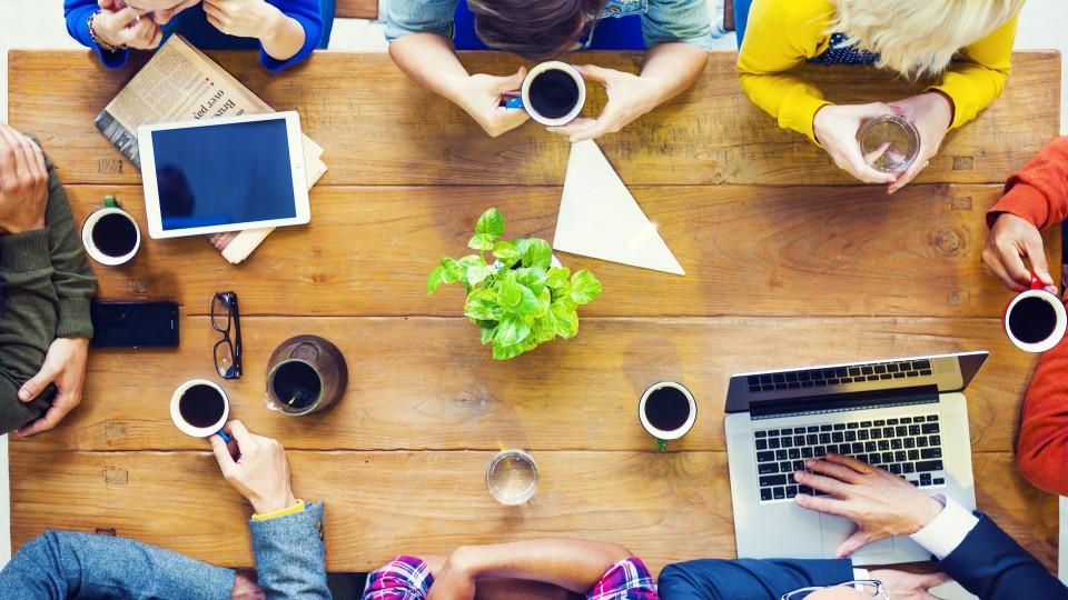 Foto: Ansicht auf ein Meeting von oben mit Tablet, Laptop und Kaffeetassen