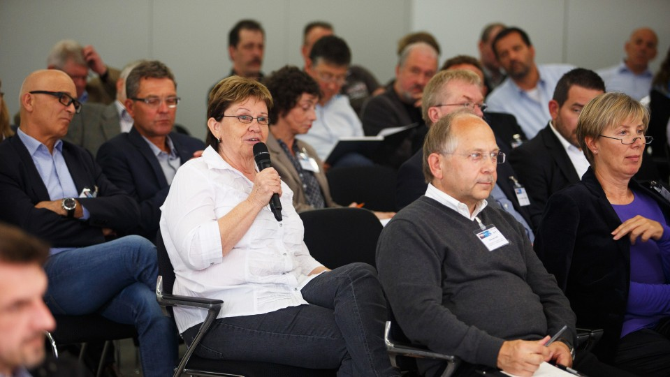 Foto: Eine Frau aus dem Publikum hält Mikrofon