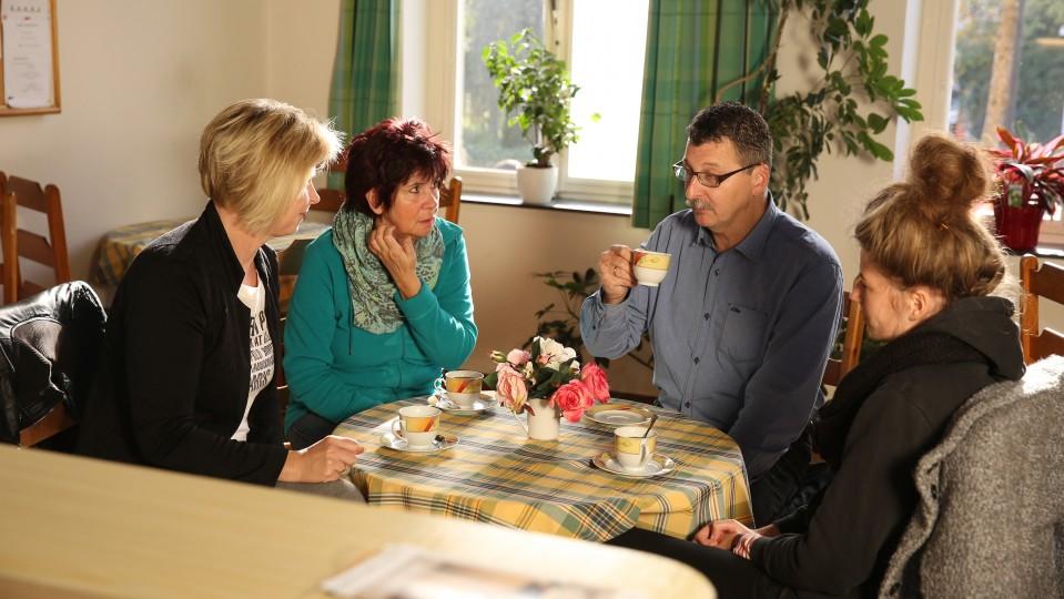 Foto: Drei Frauen und ein Mann sitzen am Tisch und trinken Kaffe