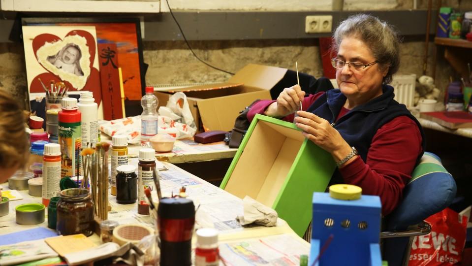 Foto: Frau bemalt eine Box
