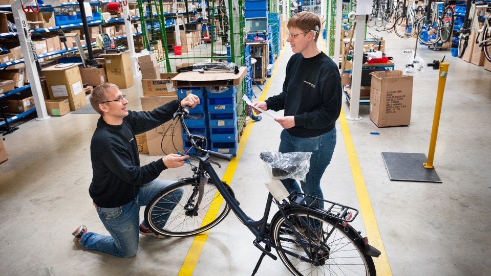 Foto: Zwei Beschäftigte mit Behinderung überprüfen vor dem Versand das Endprodukt