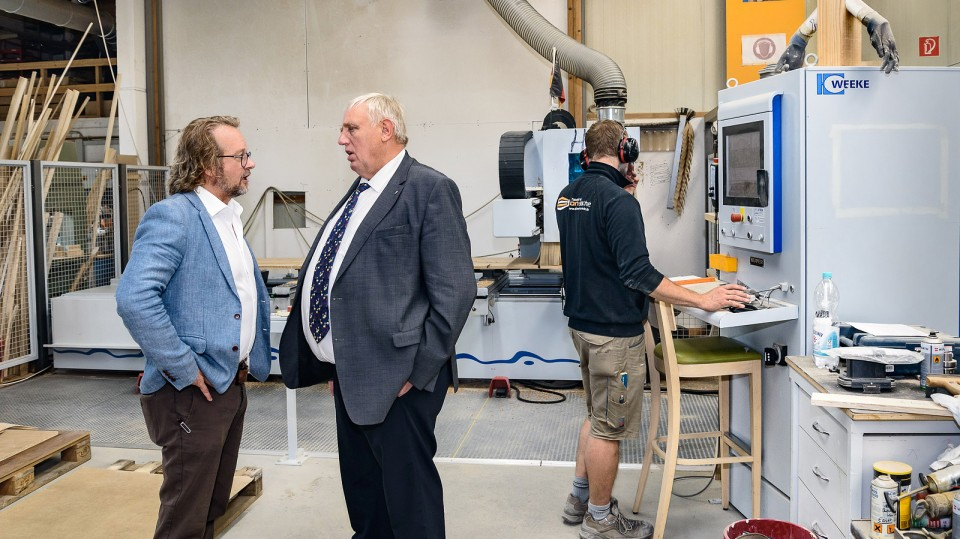 Arbeitsminister und der Geschäftsführer bei einem Betriebsrundgang