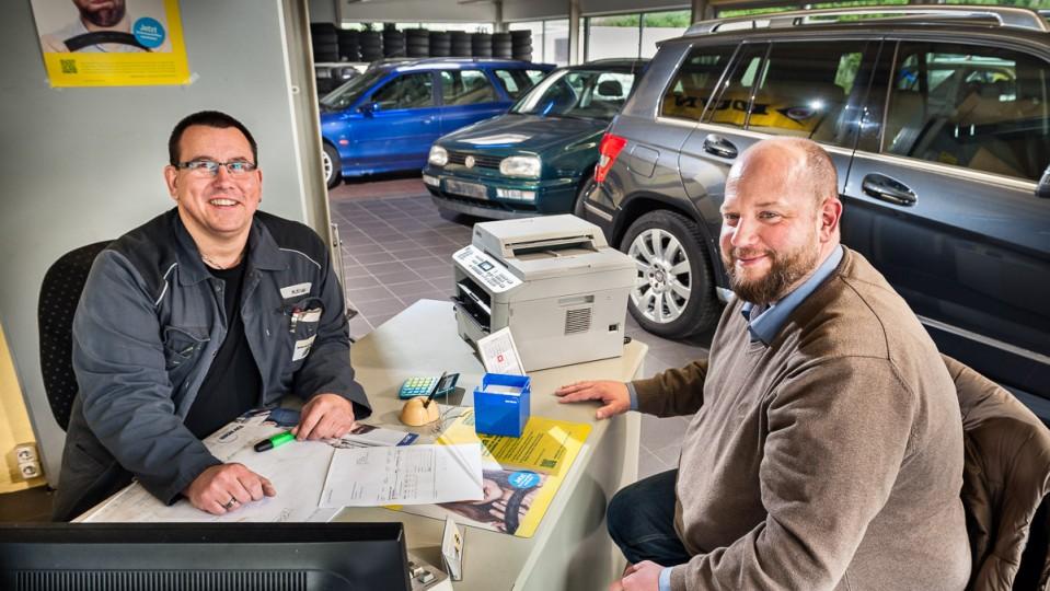 Foto: Zwei Männer sitzen am Tisch in Werkstatt