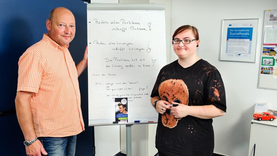 Foto: Mann und eine junge Frau vor einer Pinnwand