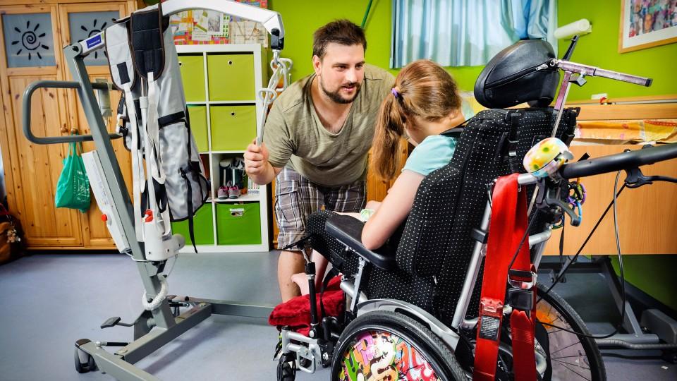 Foto: Ein Mann unterhält sich mit einer jungen Frau im Rollstuhl