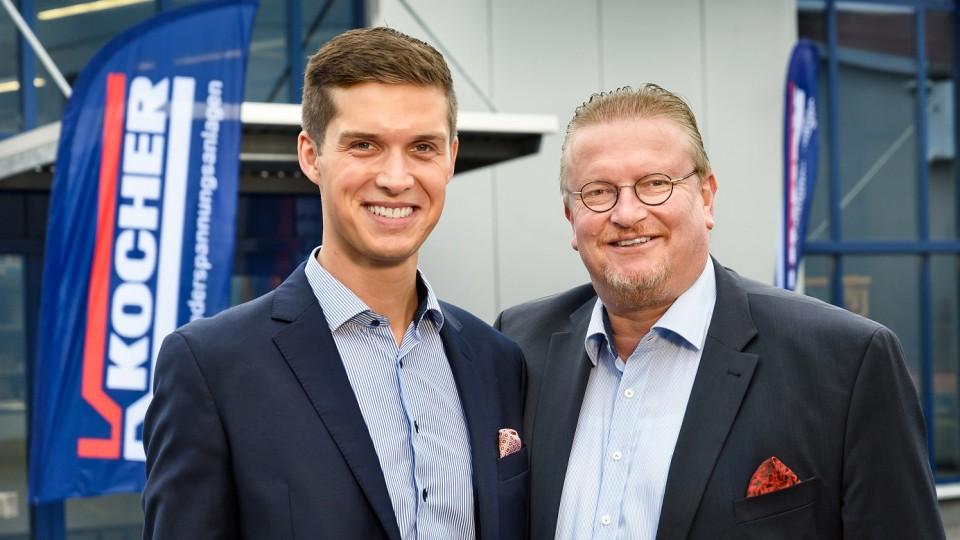 Zwei Männer stehen vor dem Gebäude der Firma Werner Kocher GmbH & Co. KG