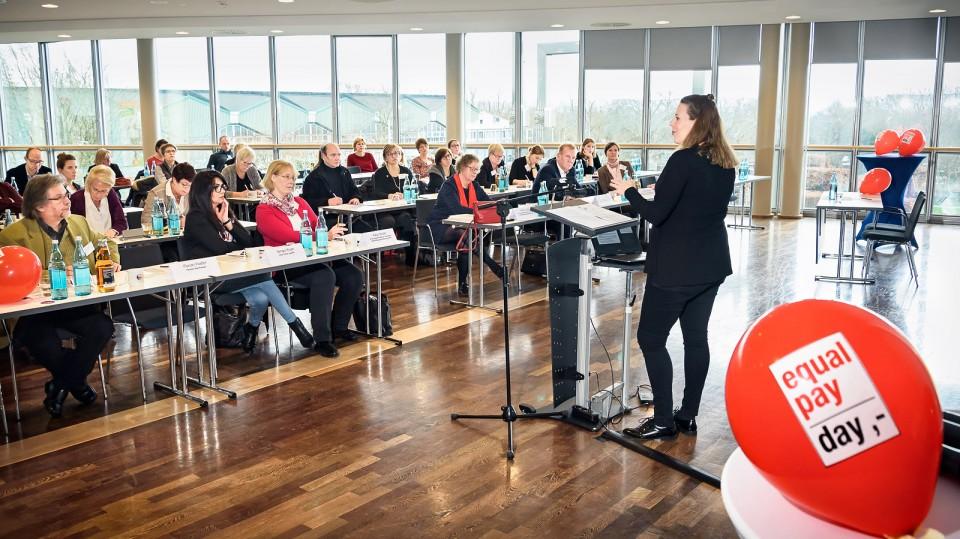 Foto: Publikum, eine Frau steht am Rednerpult