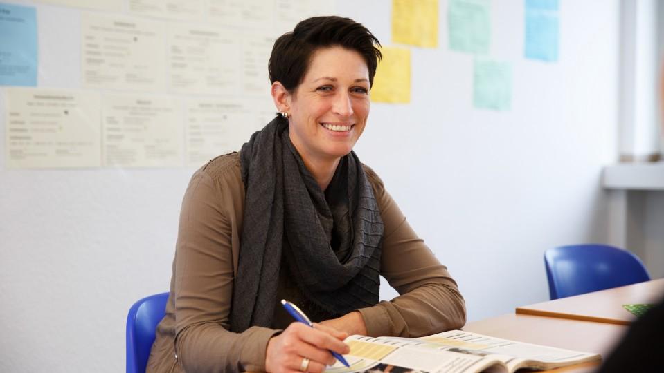 Foto: Junge Frau sitzt am Tisch und lächelt in die Kamera