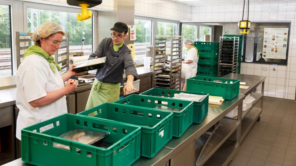 Foto: Mann und Frau sortieren Kisten mit Lebensmitteln